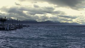 Slow motion of stormy waterscape, empty lakeside, heavy clouds above mountains. Stock footage stock video footage