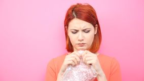 Stressed woman pops a bubble wrap to calm herself. Slow motion of stressed woman popping a bubble wrap to calm herself on pink background stock video