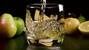 Slow motion strong alcoholic drink pour into a glass near the snack