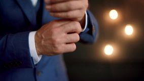 Slow motion. Stylish man in a blue suit fastening buttons on jacket preparing to go out. Close up