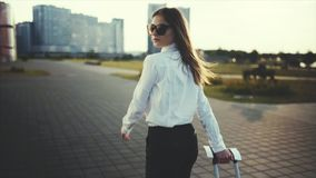 Confident woman goes to a taxi or public transport stop. Slow motion. Successful girl rolls a suitcase on wheels in the baggage claim area. Business girl with a stock video footage