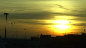 Slow motion of Sunset view in Amsterdam Schiphol international airport. Airplane waiting at gate in modern terminal with orange sky during sunrise. European stock footage