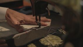 Slow motion of a tailor is practicing on his sewing machine-flat profile