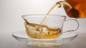 SLOW MOTION: Tea flows in a tea cup from a transparent teapot. SLOW: Tea flows in a tea cup from a transparent teapot stock footage