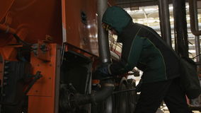 Slow Motion Technician Fixes Tube Loading Red Large Oil Tank. KAZAN/TATARSTAN/RUSSIA - NOVEMBER 15 2016: Slow motion technician fixes tube loading red large oil stock footage