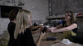 Teenage couple in a cafe shop using smartphone to pay for coffee while being friendly served by a female barista -. Slow motion of a teenage couple in a cafe stock video