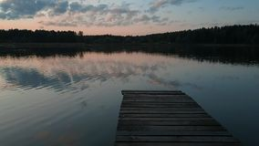 A narrow wooden pier over a lake. A slow motion to the end of a narrow wooden pier over a lake, surrounded by dark wood stock footage