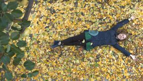 The girl among the yellow leafs. Slow motion. Top view. A young cheerful girl lies on the leaves. She looks on the up and smiles stock footage