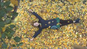 The girl among the yellow leafs. Slow motion. Top view. A young cheerful girl lies on the leaves. She looks on the up and smiles stock video footage