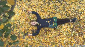 The girl among the yellow leafs. Slow motion. Top view. A young cheerful girl lies on the leaves. She opened her eyes and smiled. Leaves fall on the girl stock video