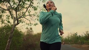 Slow motion tracking gimbal shot on young and healthy Asian Korean woman running outdoors  in wood on sunset doing jogging workout stock video