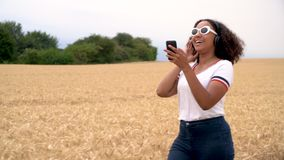 African American girl teenager young woman wearing white sunglasses walking listening to music on wireless headphones. Slow motion tracking video clip of stock footage
