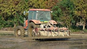 Slow Motion of tractor plowing a rice field in countryside at Tainan, Taiwan stock footage