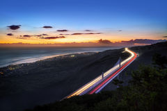 Slow motion traffic lights. Slow motion effect traffic lights on highway of the Route des Tamarins road at sunset, Reunion Island stock image