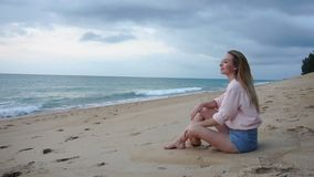 Slow motion translator young woman relaxing at sand sea beach. Slow motion translator girl sitting on sand near rolling sea waves, female come back home after stock video footage
