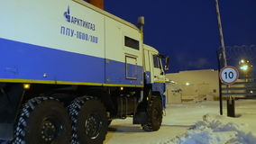 Slow Motion Truck Drives to Illuminated Enterprise Territory. KAZAN, TATARSTAN/RUSSIA - DECEMBER 20 2016: Slow motion gas company truck waits for barrier lifting stock video