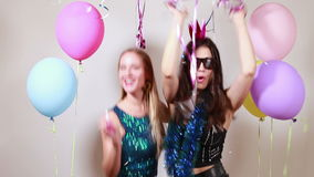 Slow motion of two attractive girls dancing in photo booth stock video