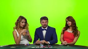 Slow motion. Two beautiful girls and man playing poker stock video footage