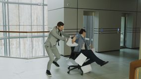 Slow motion of Two crazy businessmen riding office chair and throwing papers up while having fun in lobby of modern. Business center indoors stock footage