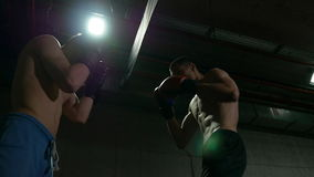 Slow motion of two fighters exercising at their left and right hits in the boxing studio ring. Slow motion shot of two fighters exercising at their left and stock video footage