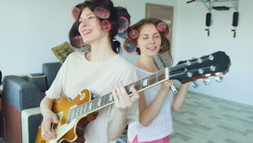 Slow motion of two funny girls singing with comb and playing electric guitar dance and sing stock footage