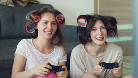 Slow motion of two funny women play console games with gamepad and have fun at home stock video footage