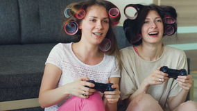 Slow motion of two funny women play console games with gamepad and have fun at home. Slow motion of two funny women play console computer games with gamepad and stock video footage