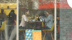 Girls with a gift in a cafe. Slow motion. Two girls are sitting in a cafe behind the glass. One girl gives another girl gift stock footage