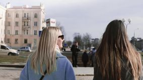 Slow motion two girls walk together in the street. Young ladies in stylish clothes with beautiful long hair. Back view. Blonde and brunette females business stock video