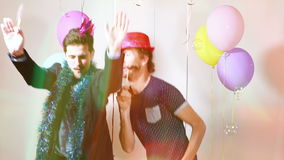 Slow motion of two happy men dancing with props in photo booth. Two smiling happy men dancing with props in photo booth, graded in slow motion stock footage