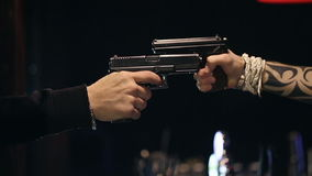 SLOW MOTION: Two male hands with guns take aim at each other. Close up stock footage