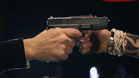SLOW MOTION: Two male hands with guns take aim at each other. Close up stock video footage