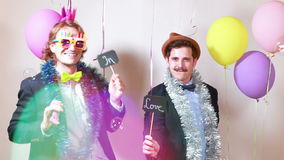Slow motion of two men holding boards in love in photo booth stock video footage