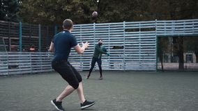 Two men practising American football on field. Slow motion of two men practising passing ball while playing American football on field stock video