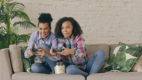 Slow motion of two mixed race curly girl friends sitting on couch play console computer games with gamepad and have fun.  stock footage