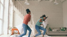 Slow motion of two mixed race young pretty girls jumping on bed and fight pillows having fun at home stock footage