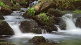 Slow Motion two way stream. A wide shot of a stream with the motion of the water blurred around moss covered rocks and stones Stock Photos