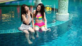 Slow motion of two women friends enjoy in swimming pool. Slow motion of two women friends enjoy in the swimming pool stock footage