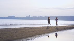 SLOW MOTION: Two women are jogging along the sandy bank of a large river. stock video footage