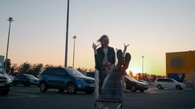 Slow motion two young millennials girl are having fun together racing on shopping carts and sparklers at supermarket
