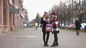 Two girls after the festive shopping consider the gifts. Slow motion. Two young pretty girls stand on the street and holding bags with shopping stock video footage