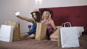 Seductive women making selfies on cellphone. Slow motion of two young seductive females sitting on bed in lingerie making self portraits in new hats on cellphone stock video footage