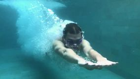 SLOW MOTION. Underwater view of professional male swimmer diving into blue water. Underwater view of a professional male swimmer diving into clear blue water stock footage