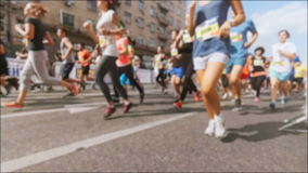 Slow motion unfocused video of marathoners run on street at hot sunny day stock video footage
