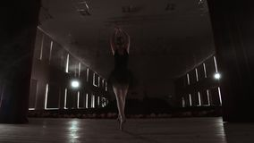 SLOW MOTION. unrecognizable beautiful ballerina performing on dark smoke stage. Blonde woman with hair in black. Ballet. Dress dancing with hands stock footage