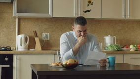 Slow motion of upset young man reading letter with unpaid bill in the kitchen at home