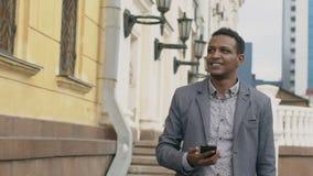 Slow-motion van jonge gelukkige zakenman gebruikend smartphone en in openlucht kijkend rond straat stock video