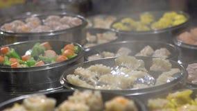 Slow motion Vendor selling Dumpling and Shaomai in Asian Street Food Market. Slow motion vendor preparing and selling Shaomai and customers at Asian Street Food stock footage