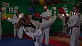 Slow motion video of an adult taekwondo training session in the gym, a woman kicking, selective focus