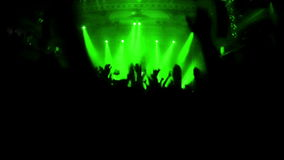 Slow motion video of cheering crowd during rock-concert. Green spotlights illuminating the venue. stock video